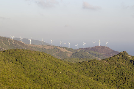 Wind turbines of a wind farm on the wooded mountain peaks of Andalusia in Spain off the Bay of Gibraltar