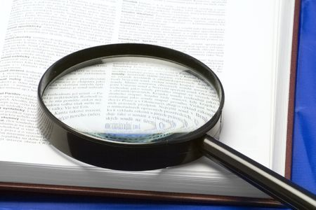 multiplying: magnifying glass on a book - close-up