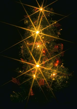 a christmas tree with electric candles on the black background