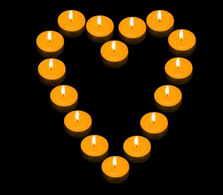 candlelit: a group of burning candles forming a fiery heart on the black background