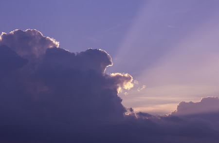 big behind: Cloud. Big purple cloud on the clear blue sky. The suns rays shine from behind a cloud.