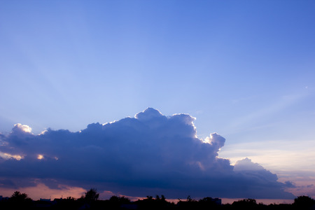big behind: Cloud. Big purple clouds on blue sky background. The suns rays shine from behind a cloud. Stock Photo