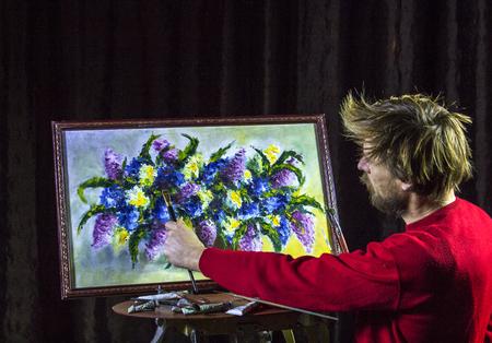 赤いセーターを着た男のひげを生やしたアーティストが、スタジオのイーザーに花を描く芸術的なブラシを描く