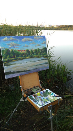 Easel sketchbook with palette oil painting on background of a river water pond plain air. The artist workplace in open air.