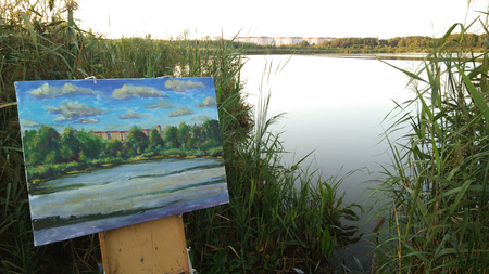Easel sketchbook with oil painting on background of a river water pond plain air. The artist workplace in open air.