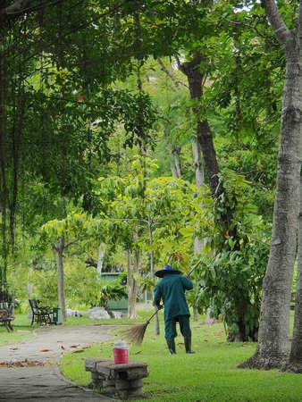 broom handle: A Gardener Removes Fallen Leaves With Wooden Long Handle Broom