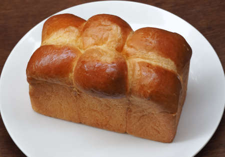 unsliced: Big Loaf Of Bread On White Plate Stock Photo