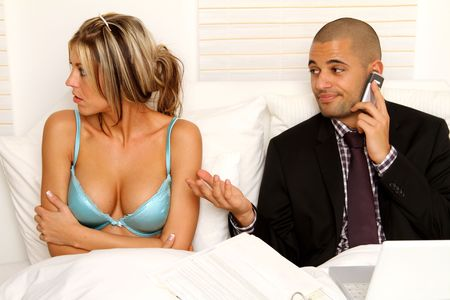 workaholic: Workaholic with his annoyed wife in bedroom