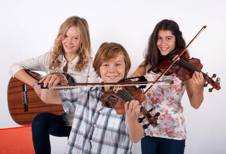 twee meisjes en een jongen spelen van muziek instrumenten Stockfoto