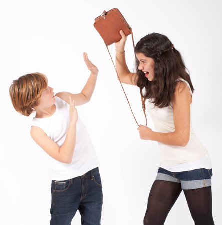 brother sister fight: girl is threatening a boy with her handbag Stock Photo