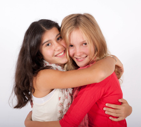 two girls hugging: two girls hugging each other Stock Photo