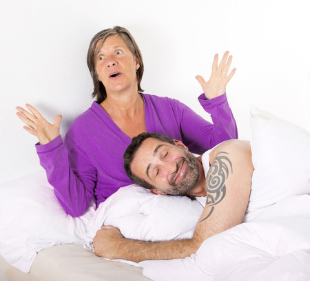 man is sleeping and smiling and woman is upset