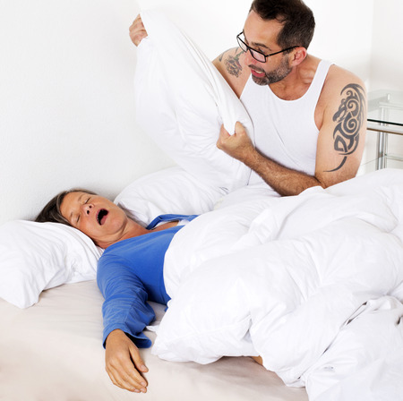tatoos: couple in bed. woman is sleeping and man is upset