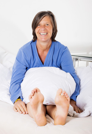 woman sitting in bed showing her bare feet and smiling Stock Photo
