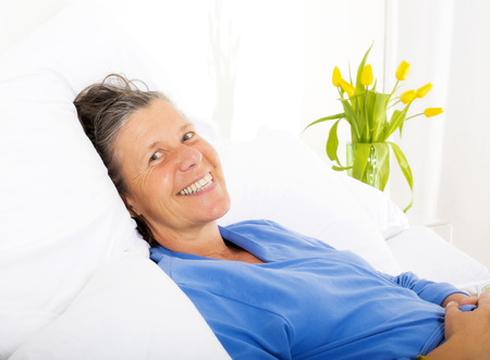 rested: woman lying in bed and smiling