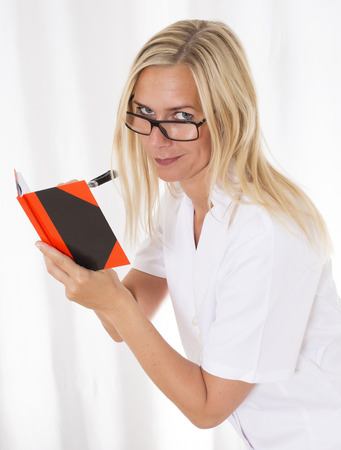 portrait of a blond woman writing in a notebook photo