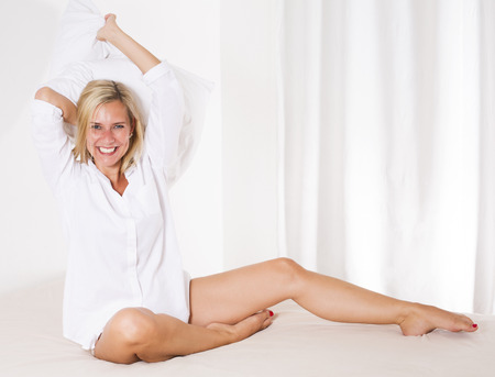 wellness sleepy: blond woman in bed with a big pillow in her hands and smiling