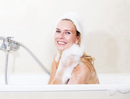 bodywash: blond woman sitting in bathtub covered with foam