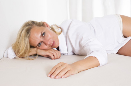 wellness sleepy: blond woman in a white shirt is lying in bed and smiles Stock Photo