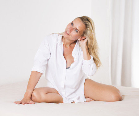 wellness sleepy: blond woman in a white shirt is sitting in bed and smiles