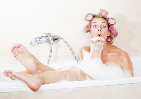 bodywash: blond woman sitting in bathtub with curlers in her hair Stock Photo