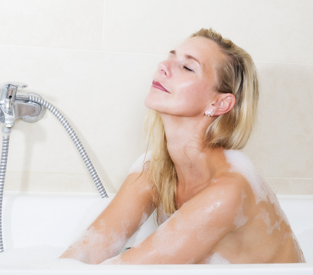 bodywash: blond woman sitting in bathtub and is relaxing with her eyes closed Stock Photo