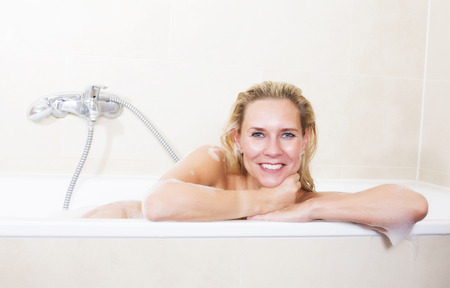 bodywash: blond woman sitting in bathtub and smiling Stock Photo