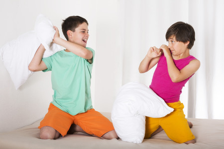 two boys having a pillow fight and laughing photo