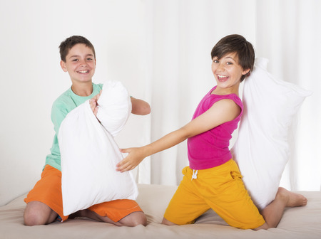 sleepover: two boys having a pillow fight and laughing