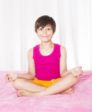 yoga pillows: young boy sitting in bed and smiling
