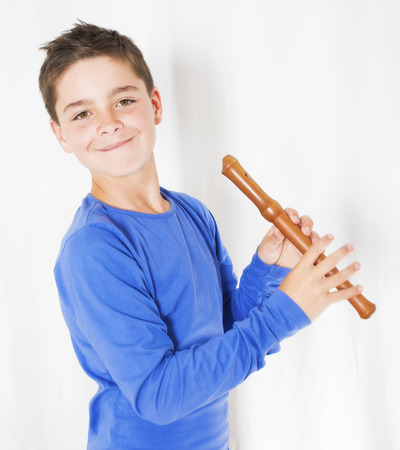 young boy holding a flute in his hand and is smiling