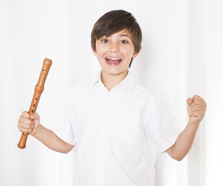 portrait of a boy holding a flute in his hands and smiling Stock Photo