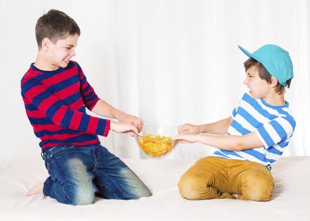 peleando: dos ni�os peque�os en la cama y la lucha sobre un taz�n de papas fritas