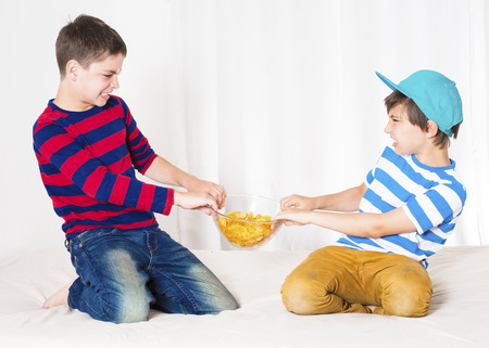two young boys in bed and fighting over a bowl of potato chips Stock Photo