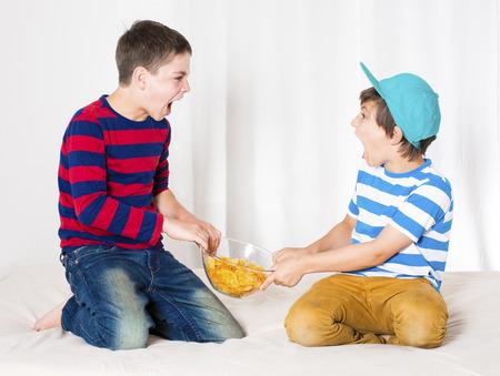 twee jonge jongens in bed en vechten om een kom van chips Stockfoto