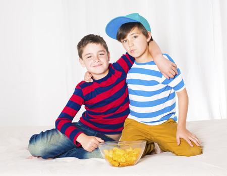 boy bedroom: two kids in bed eating potato chips