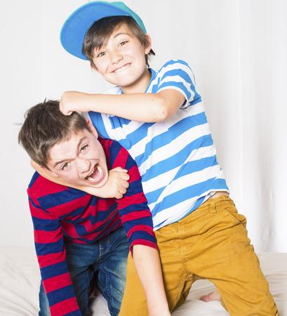 twee jonge jongens in bed en vechten Stockfoto