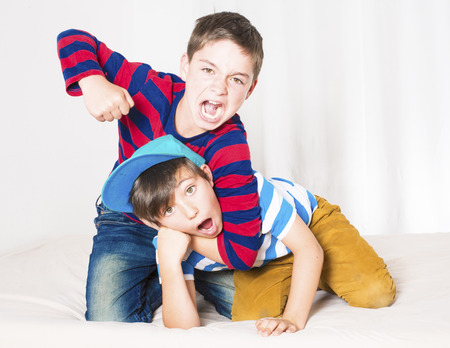 two young boys in bed and fighting photo