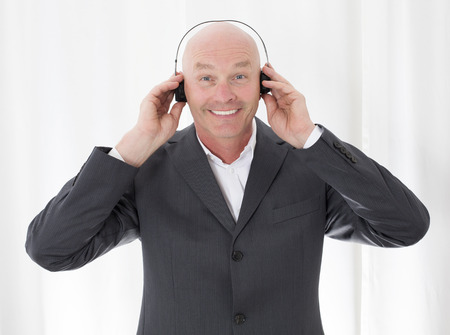 man in a suit with headphones and a big smile photo