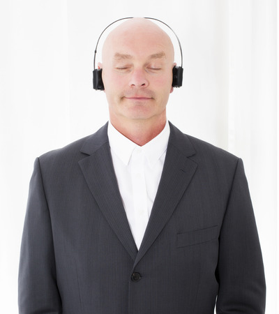 man in a suit with headphones and his eyes closed photo
