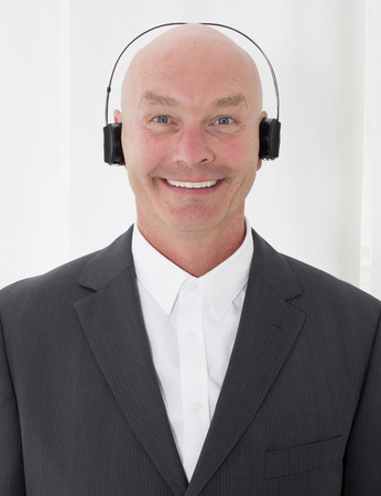 bald-headed businessman with headphones and a big smile photo