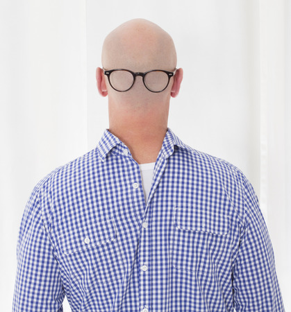 bald man: back of a bald-headed man in a blue shirt in reverse with glasses