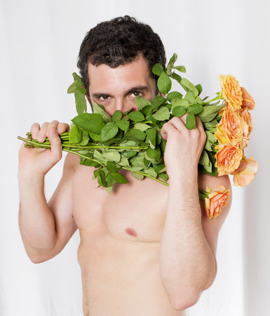 anniversary sexy: portrait of a latin man holding a bouquet of roses