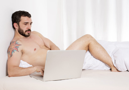latin man with torso lying in bed with laptop photo