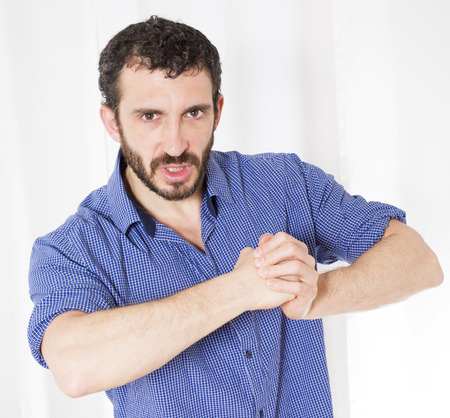 aggresive: bearded man in blue shirt holding up his fists Stock Photo