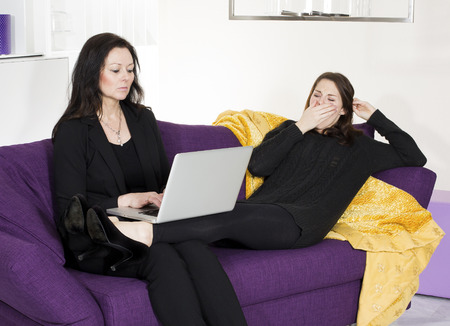 woman sitting on couch with a laptop while another woman is bored and yawns photo