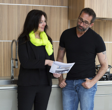 woman in businesssuit consults a man standing in ktchen