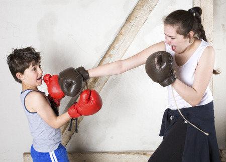 sibling rivalry: young boy and teenage girl with braces are boxing