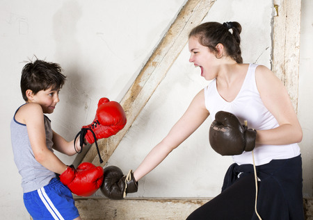 young boy and teenage girl with braces are boxing photo