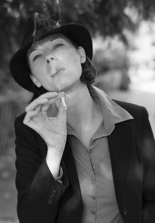woman in suit and hat is smoking a cigarette photo